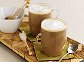 Two glasses of cafe au lait, cafe latte with crystal sugar sticks