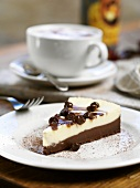 A slice of cheesecake with a cappuccino