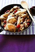 Chicken pieces braised in white wine sauce with tomatoes & olives