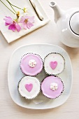 Cupcakes decorated with hearts & sugar flowers (overhead view)