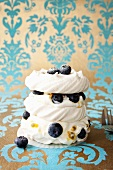 Meringues with blueberries, cream and passion fruit sauce