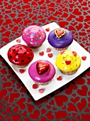 Muffins with coloured icing and hearts