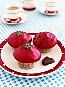 Muffins with red icing and chocolate hearts, with tea