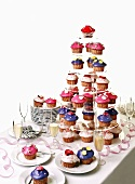Colourful muffins on a tiered stand with sparkling wine