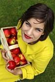 Frau hält Spankorb mit frischen roten Äpfeln