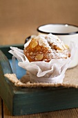 Almond muffin and enamel mug on wooden tray