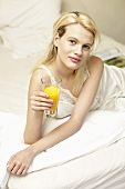 Young woman with a glass of orange juice in bed