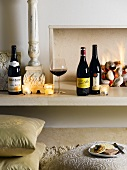 Bottles of red wine, glass of wine and tealights in front of fire