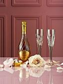 Champagnerflasche, Trüffelpralinen, Rosen und Sektgläser