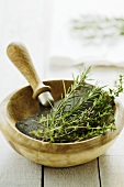 Rosemary and thyme in wooden bowl with mezzaluna