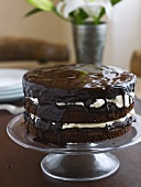 Chocolate cake with whipped cream filling on cake stand
