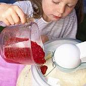 Little girl pouring fruit into ice cream maker