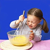 Little girl whisking egg yolks in bowl