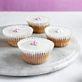 Four cupcakes with sugar flowers on marble plate