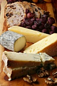Cheese board with walnuts, dried grapes and bread