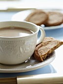 Tea with milk in cup and saucer, biscuits in saucer