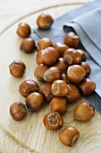 Unshelled hazelnuts on wooden board
