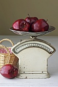 Several red apples on old kitchen scales