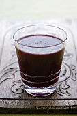 A glass of apple, blackberry and pear juice