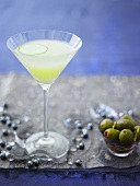 Martini with slice of cucumber, green olives