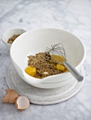 Brown sugar and egg yolks in bowl with whisk