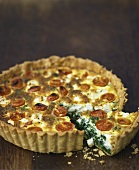 Cheese, spinach and tomato quiche, a piece cut