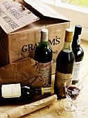 Various bottles of red wine in front of cardboard box