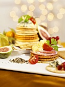 Crackers with cheese, ham, tomatoes and figs (Christmas)