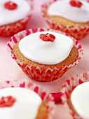 Fairy cake decorated with white icing sugar and a red sugar flower