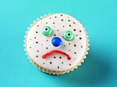 Fairy cake decorated with a sad, spotty face