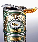 Golden syrup in the tin and on a spoon