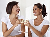 Two women toasting with white wine glasses