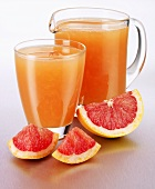 Pink grapefruit juice in a glass and a glass jug