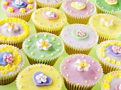 Lots of pastel-coloured fairy cakes decorated with sugar flowers