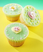 Fairy cakes with green icing and sugar flowers
