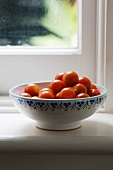 A bowl of cherry tomatoes on a window sill