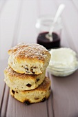 Raisin scones with clotted cream and jam in the background