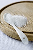 Sugar and a spoon on a wooden board
