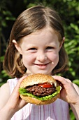 A girl holding a hamburger