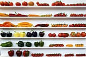 Various tomatoes and pepper on a shelf