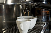 Espresso flowing into two cups