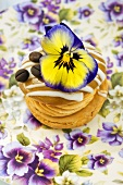 A whoopie pie decorated with a pansy and a coffee bean