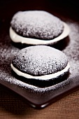 Two chocolate whoopie pies with icing sugar