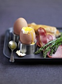 Boiled eggs with green asparagus and ham