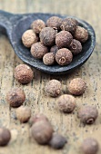 Allspice berries with a wooden spoon