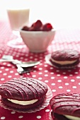 Raspberry whoopie pies on a spotted tablecloth with fresh raspberries, a glass of milk and cutlery