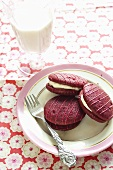 Raspberry whoopie pies on a plate with a fork and a glass of milk