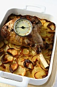 Roasted leg of lamb on a bed of sliced potatoes