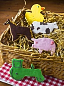 Humorous cookies (animal shapes, tractor) in a wicker basket