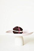 Chocolate Whoopie pie, wrapped with string, on a cake stand
